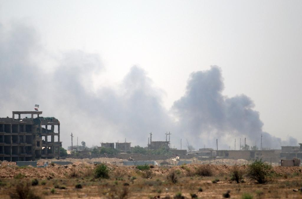 Smoke rises from buildings in Fallujah as Iraqi government forces clear the streets of city from road-side bombs and booby-traps on June 23, 2016 (AFP Photo/Haidar Mohammed Ali )