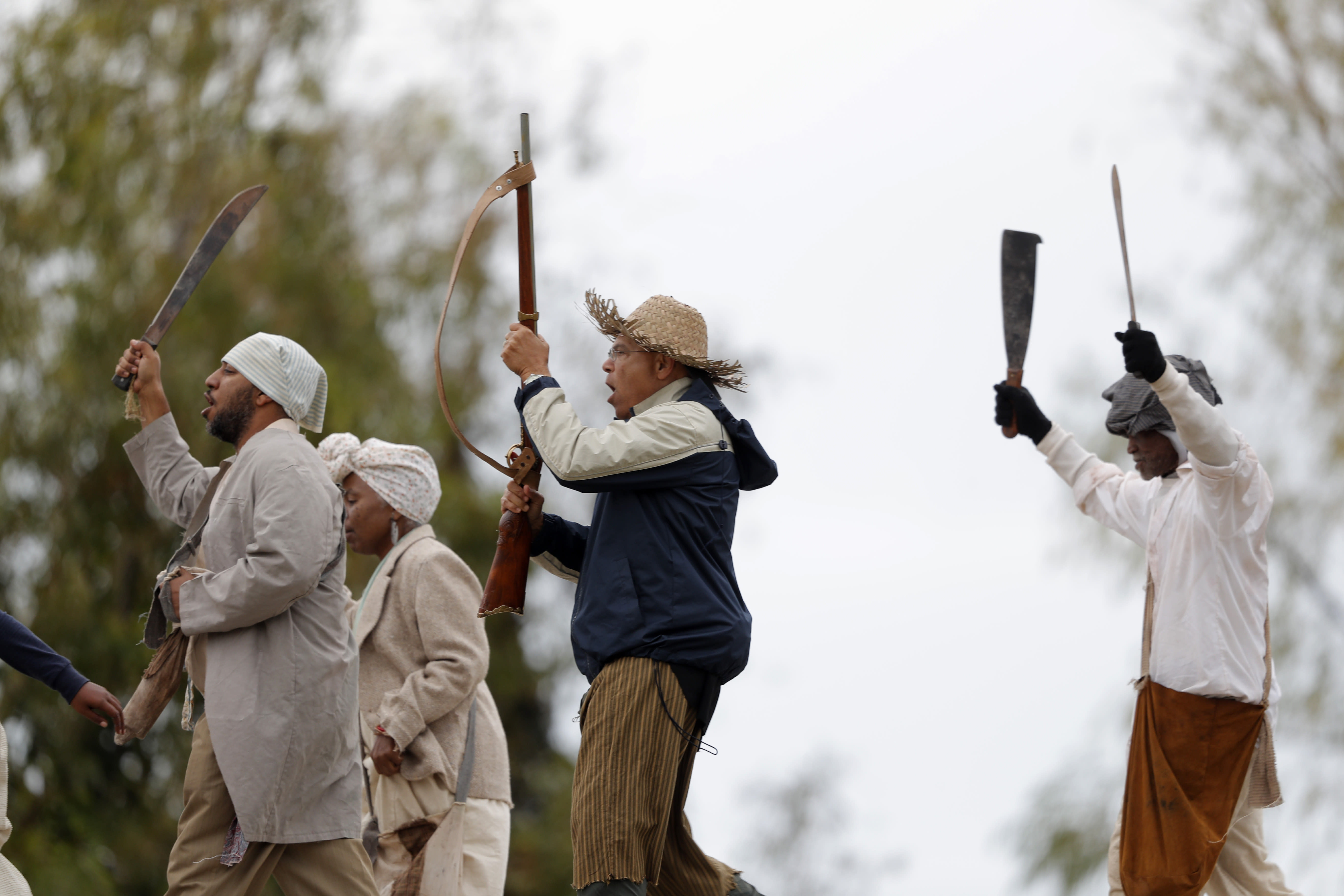People march along the Mississippi River levee as they participate in a reenactment of the largest slave rebellion in U.S. history, in LaPlace, La., Friday, Nov. 8, 2019. The reenactment was conceived by Dread Scott, an artist who often tackles issues of racial oppression and injustice. (AP Photo/Gerald Herbert)