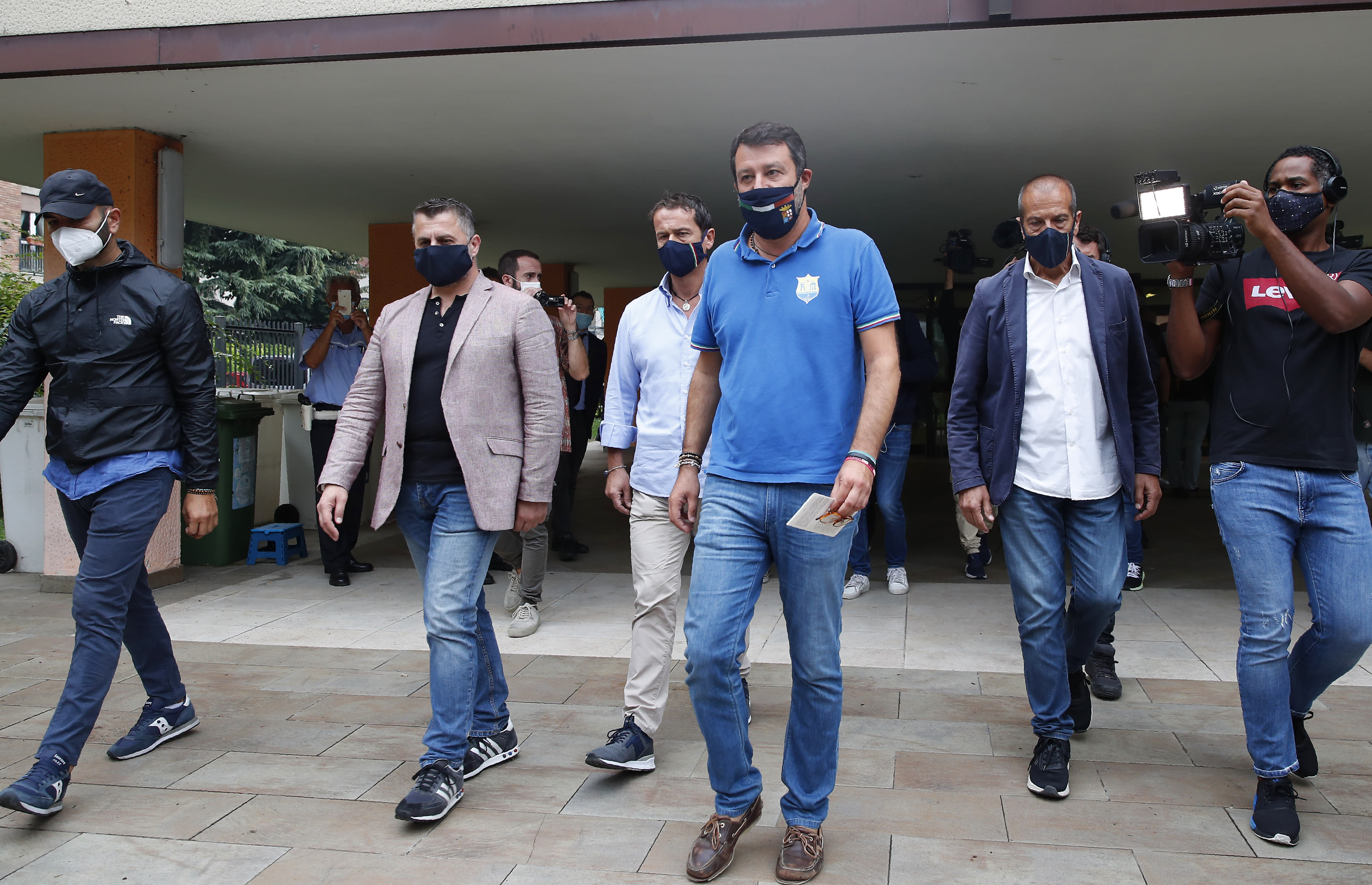 Right-wing opposition leader Matteo Salvini,center, leaves a polling station, in Milan, Italy, Monday, Sept. 21, 2020. On Sunday and Monday Italians are called to vote nationwide in a referendum to confirm a historical change to the country's constitution to drastically reduce the number of Members of Parliament from 945 to 600. Eighteen million of Italian citizens will also vote on Sunday and Monday to renew local governors in seven regions, along with mayors in approximately 1,000 cities. (AP Photo/Antonio Calanni)
