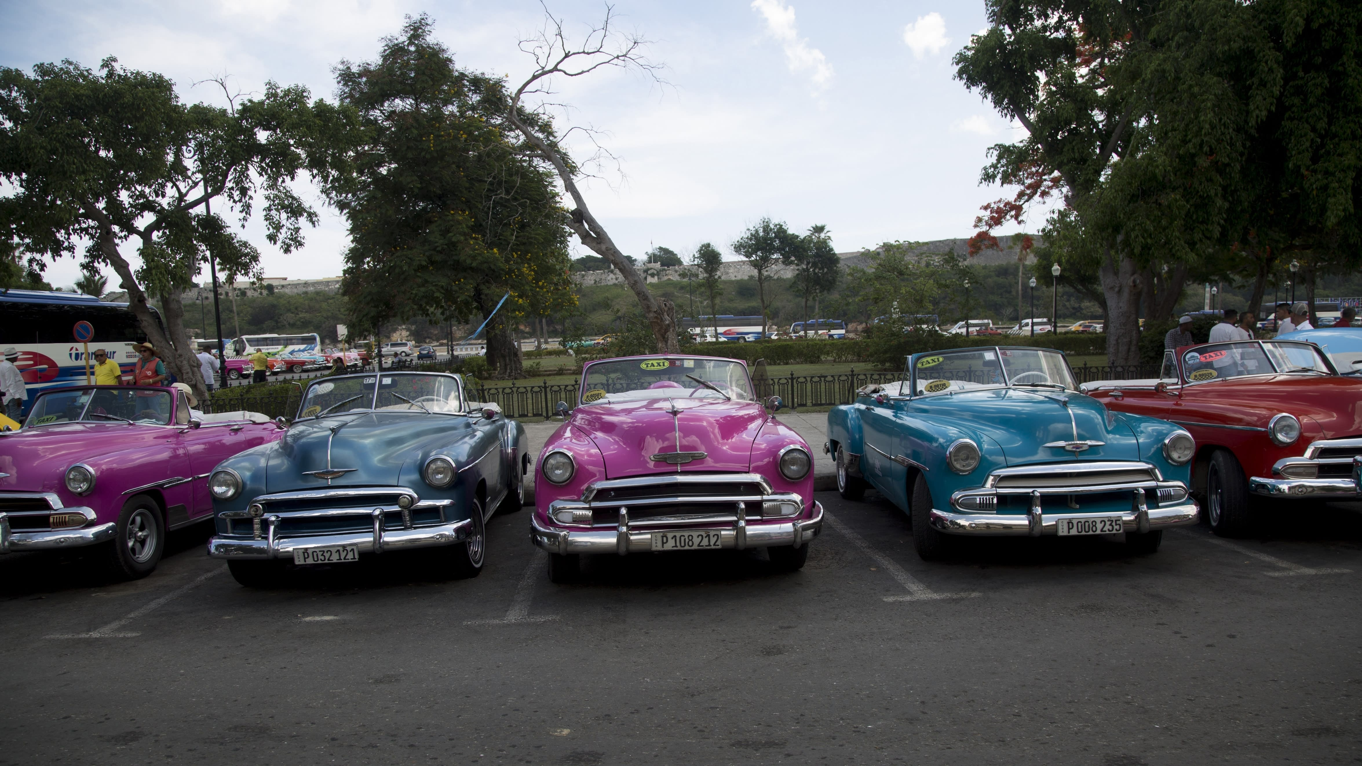Classic American cars sit parked as their drivers await tourists in Havana, Cuba, Wednesday, June 5, 2019. Drivers of classic cars, owners of private restaurants, guides, handicrafts vendors and owners of rooms for rent will be among the most affected by the Trump administration's new restrictions on travel to Cuba. (AP Photo/Ismael Francisco)