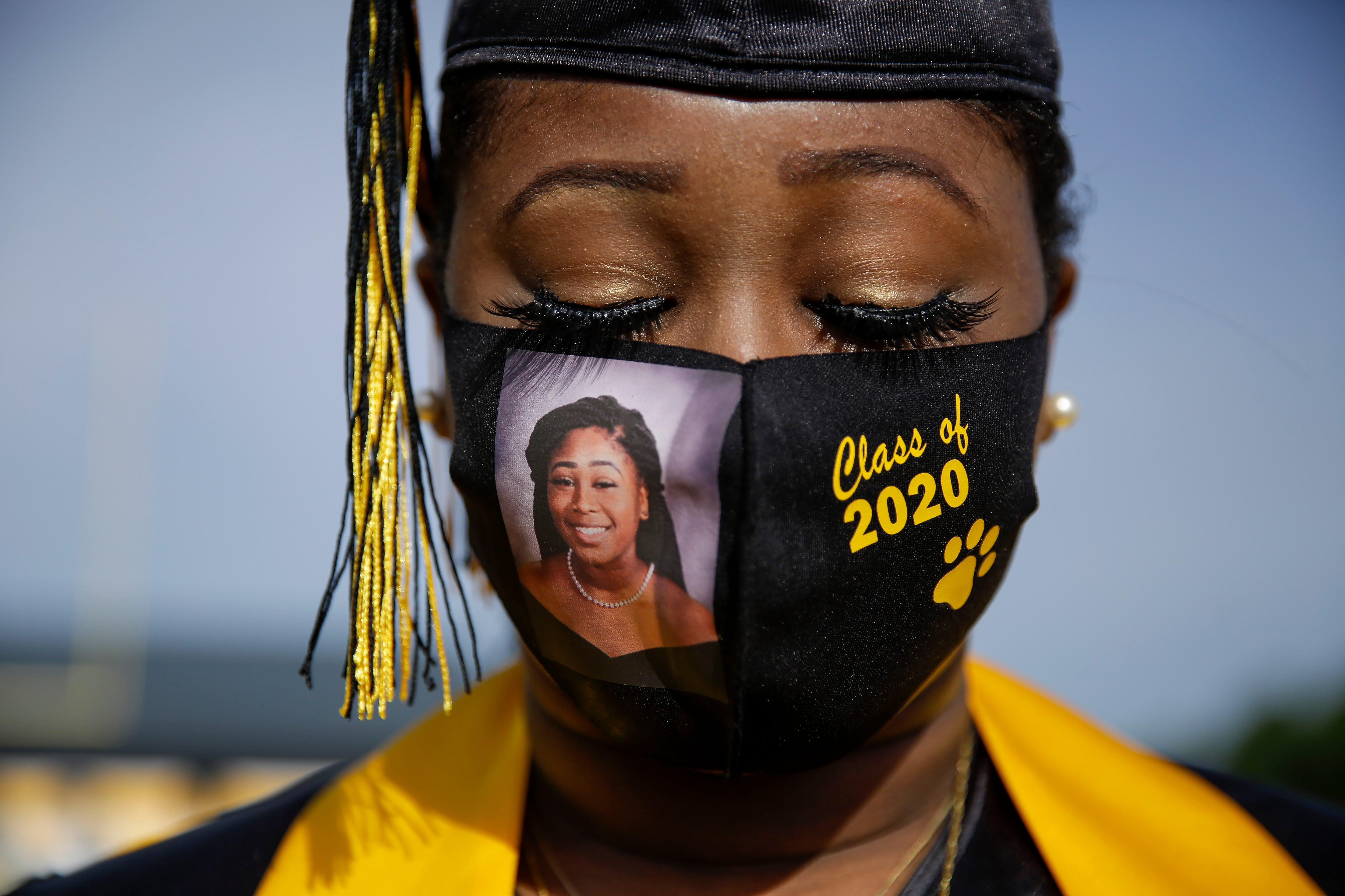 Senior Yasmine Protho, 18, wears a photo of herself on her mask while graduating with only 9 other classmates from Georgia's Chattahoochee County High School last May. A very small number of family members were allowed to attend.