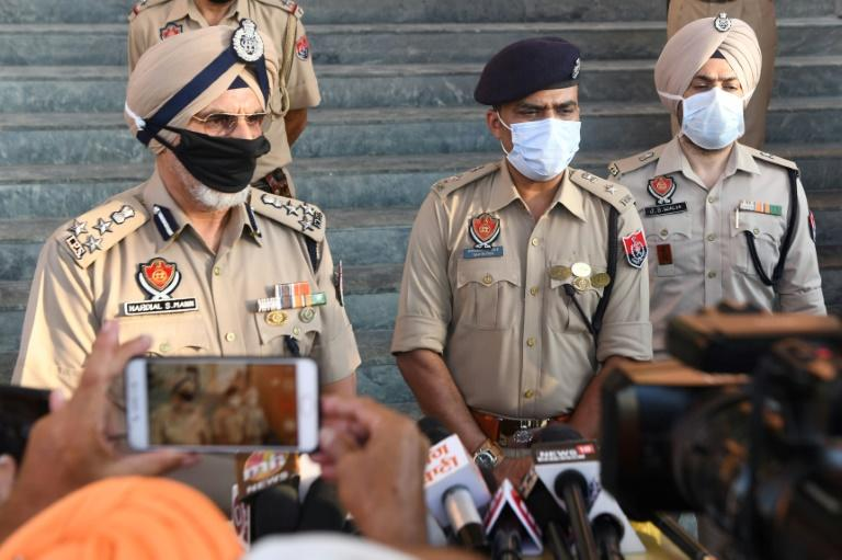 Punjab Police speak to media in Tarn Taran district on August 1, 2020 after dozens of people died from poisoned alcohol (AFP Photo/NARINDER NANU)