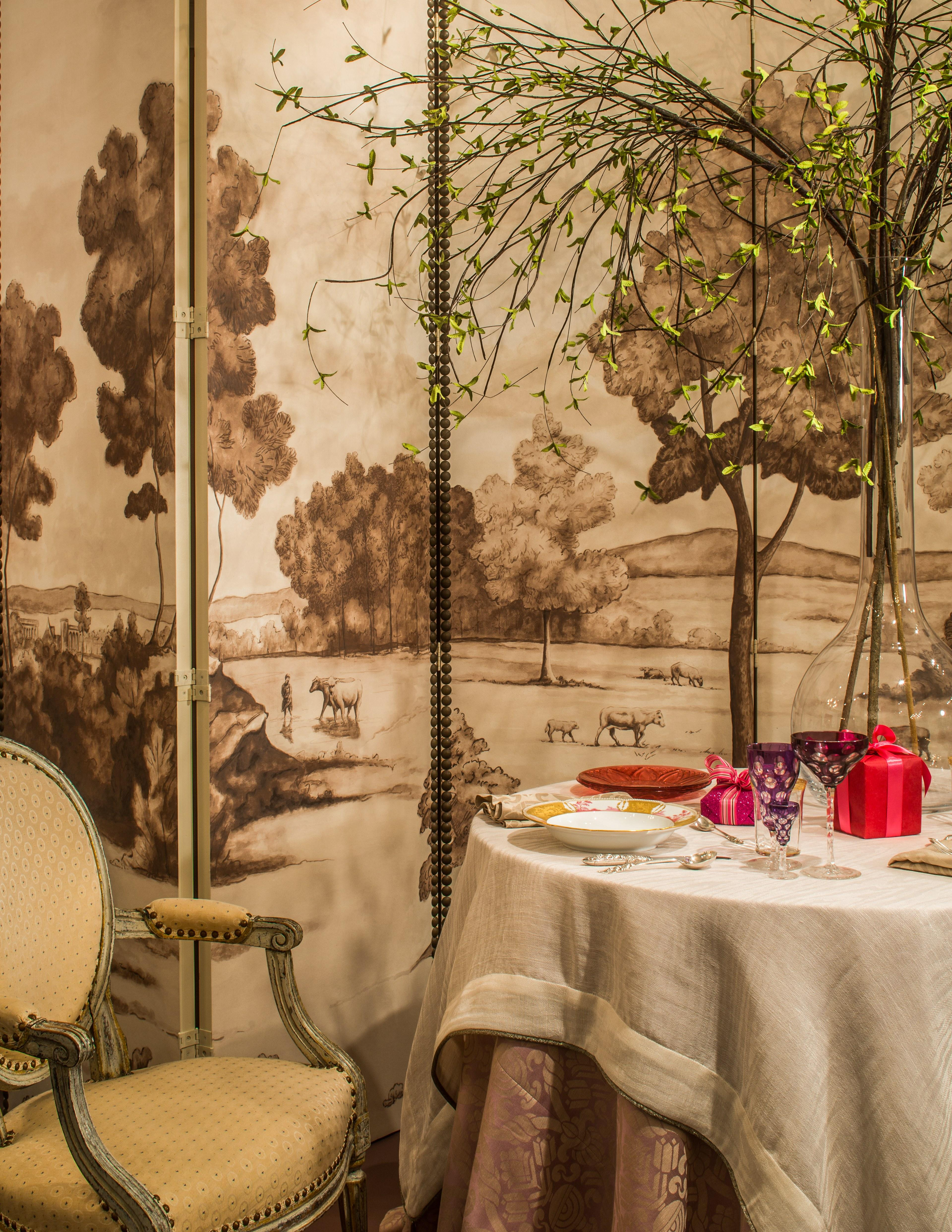 """""""It's such a pleasure to get to use these things we don't see every day,"""" marvels Virginia-based Dixon. To highlight the china he selected, the designer opted not to go all out, but rather to use neutral, understated visuals that let Post's treasures take center stage. """"We were imagining a romantic dinner for two in honor of Valentine's Day,"""" he says. He set the scene with fabrics from his line for Vervain and vintage chairs, then added an additional personal note with silverware his family bought in Thailand and heirloom glasses. """"I love the idea of my grandmother's glassware sitting next to these incredible heirlooms from imperial Russia,"""" he says."""