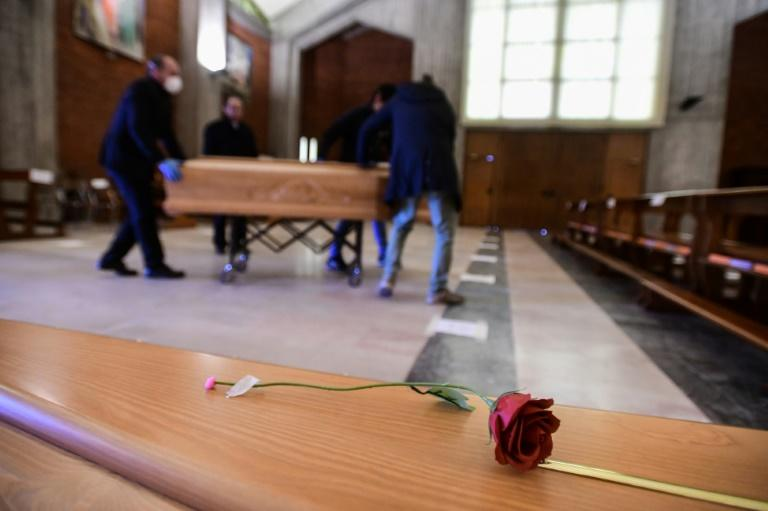 A single red rose rested atop a coffin at a warehouse in the commune of Ponte San Pietro on Bergamo's western outskirts (AFP Photo/Piero CRUCIATTI)