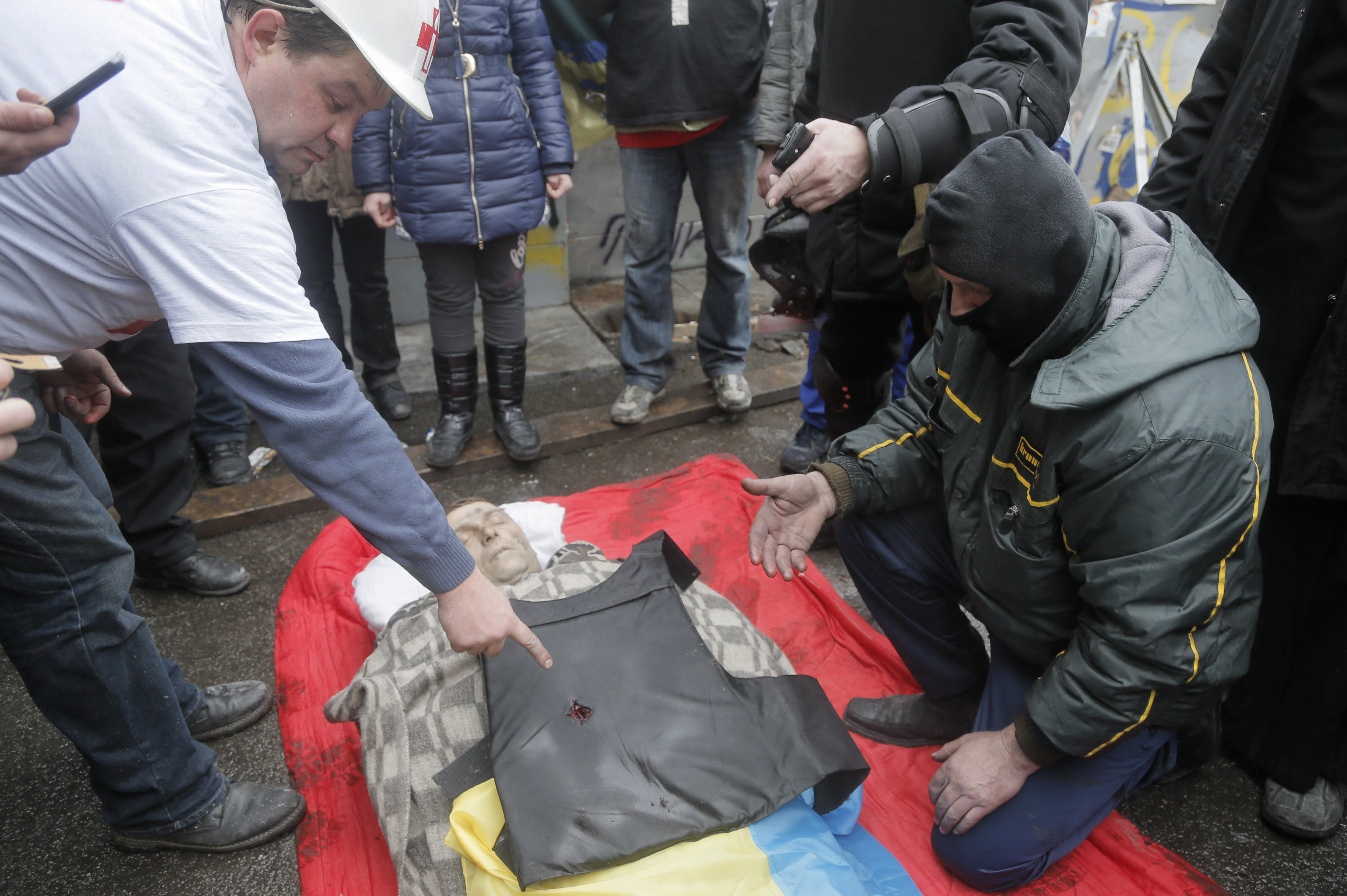 FILE- In this Thursday, Feb. 20, 2014 file photo, people look at a bullet hole in victim's vest who was killed during a clash between riot police and protesters in Independence Square, the epicenter of the country's current unrest in Kiev, Ukraine. As questions circulate about who was behind the lethal snipers that sowed death and terror in Ukraine's capital, doctors and others told the AP the similarity of bullets wounds suffered by opposition victims and police indicates the snipers were specifically trying to stoke tensions and spark a larger, angrier clash between opposition fighters and government security forces. (AP Photo/Efrem Lukatsky, file)