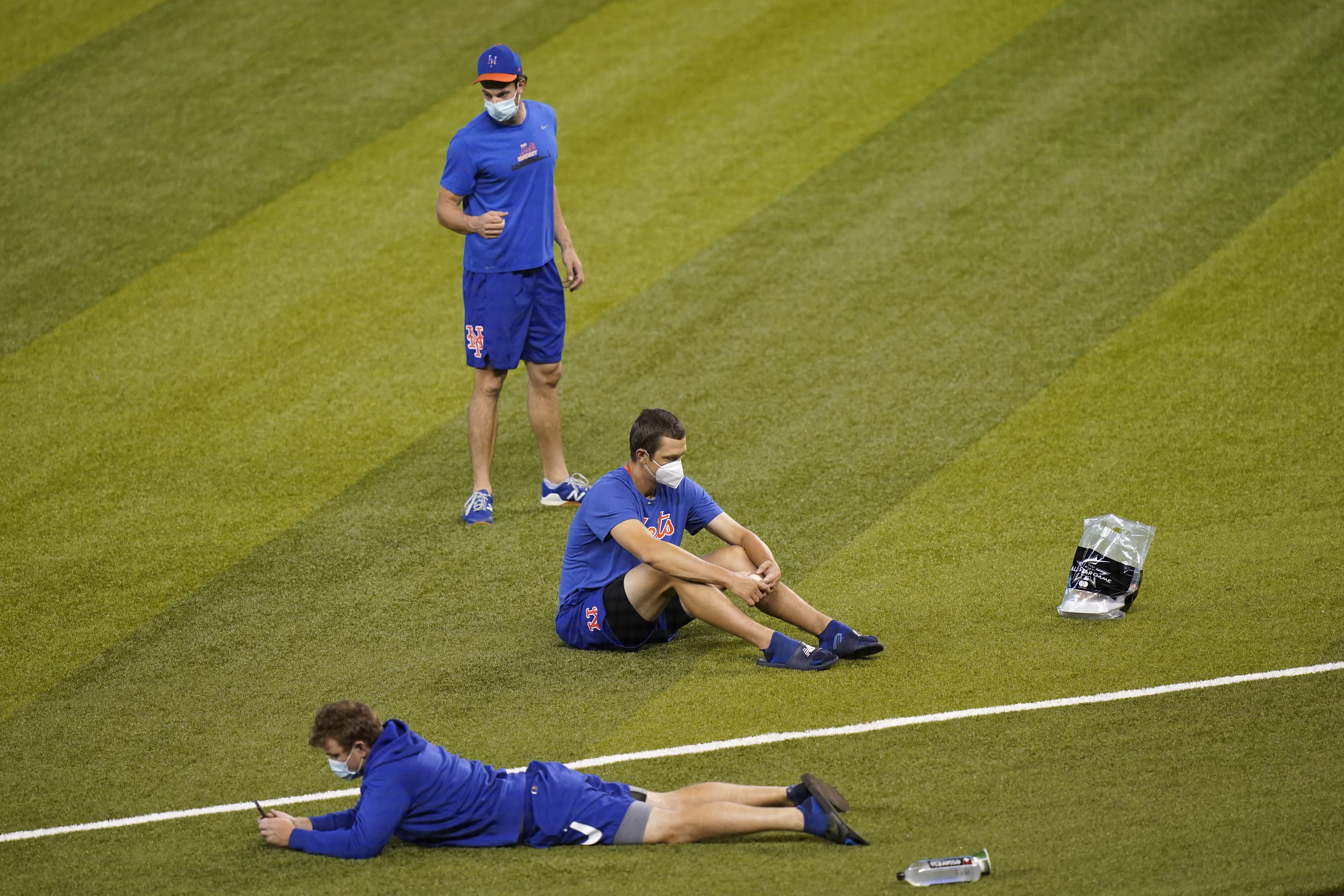 New York Mets players sit on the field before a baseball game against the Miami Marlins, Thursday, Aug. 20, 2020, in Miami. Major League Baseball says the Mets have received two positive tests for COVID-19 in their organization, prompting the postponement of two games against the Marlins. (AP Photo/Lynne Sladky)