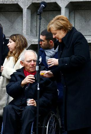 German Chancellor Angela Merkel and Bundestag's President Wolfgang Schaeuble attend the inauguration of memorial at the site of last year's truck attack in a Christmas market, which killed 12 people and injured many others, at Breitscheidplatz square in Berlin, Germany December 19, 2017. REUTERS/Fabrizio Bensch