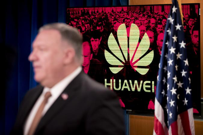 """A monitor displays the logo for Huawei behind Secretary of State Mike Pompeo as he speaks during a news conference at the State Department in Washington,DC on July 15, 2020. - US Secretary of State Mike Pompeo said Wednesday he will visit Britain and Denmark next week, days after London pleased Washington with a ban on Chinese telecom giant Huawei. """"I leave on Monday for a quick trip to the United Kingdom and Denmark, and I'm sure that the Chinese Communist Party and its threat to free peoples around the world will be high on top of that agenda,"""" Pompeo told a news conference. (Photo by Andrew Harnik / POOL / AFP) (Photo by ANDREW HARNIK/POOL/AFP via Getty Images)"""
