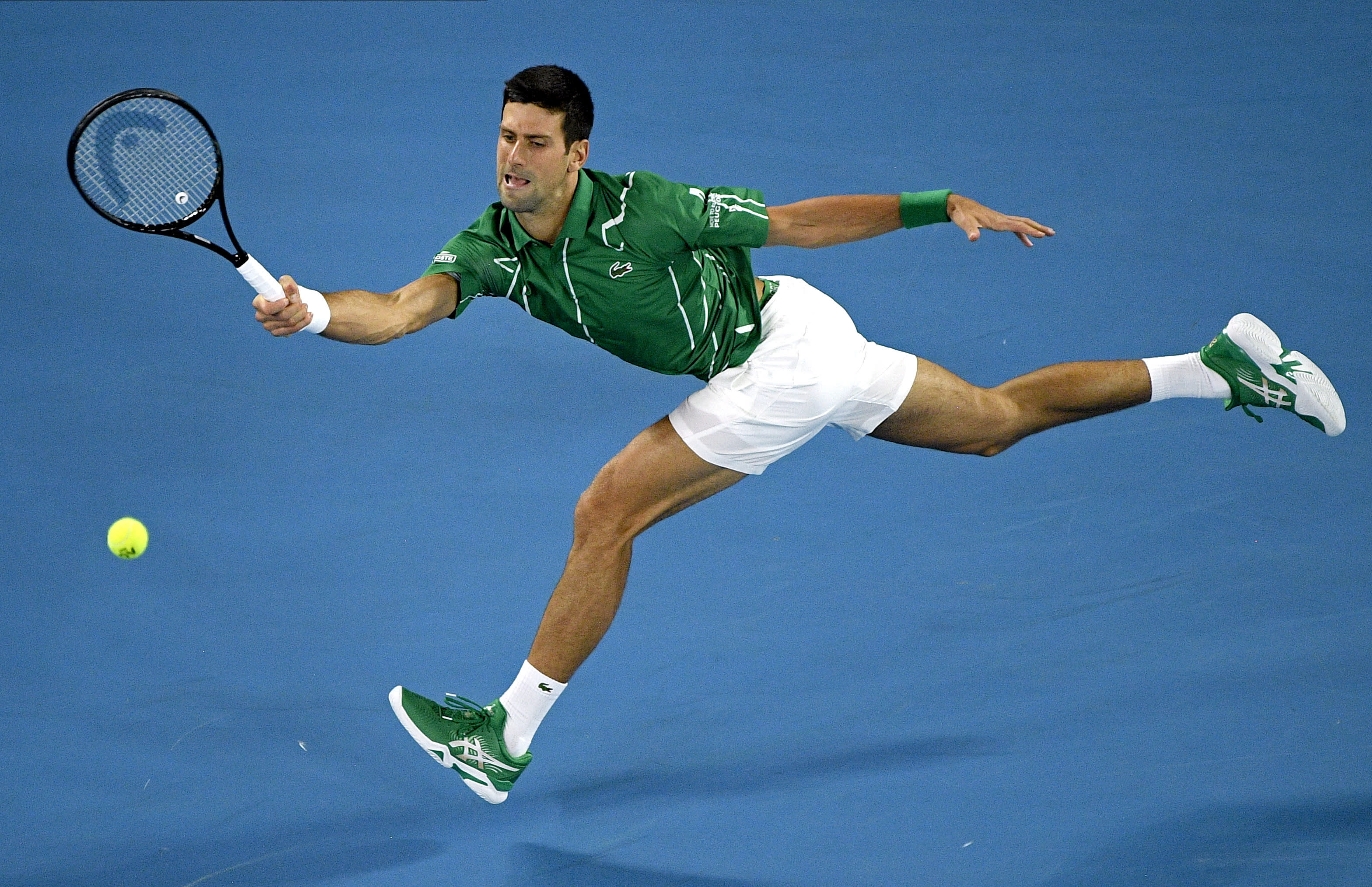 FILE - In this Monday, Jan. 20, 2020, file photo, Serbia's Novak Djokovic makes a forehand return to Germany's Jan-Lennard Struff during their first round singles match the Australian Open tennis championship in Melbourne, Australia. Djokovic is scheduled to play in the U.S. Open, scheduled for Aug. 31-Sept. 13, 2020. (AP Photo/Andy Brownbill, File)
