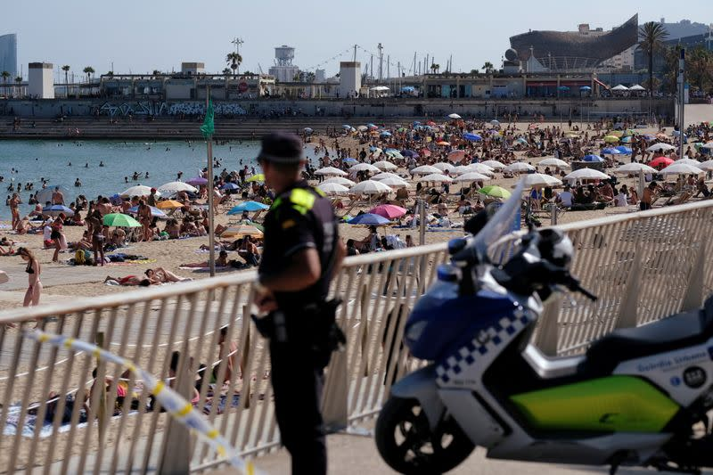 FILE PHOTO: A police officer looks on as people enjoy the sunny weather on the beach, as Spain officially reopens the borders amid the coronavirus disease (COVID-19) outbreak, in Barcelona