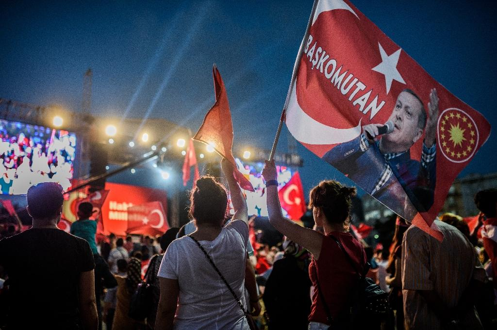 "A pro-Erdogan supporter holds a portrait flag of Turkish President Recep Tayyip Erdogan reading ""Commander in Chief"" during a rally against the military coup on Taksim square in Istanbul on July 25, 2016 (AFP Photo/Ozan Kose)"