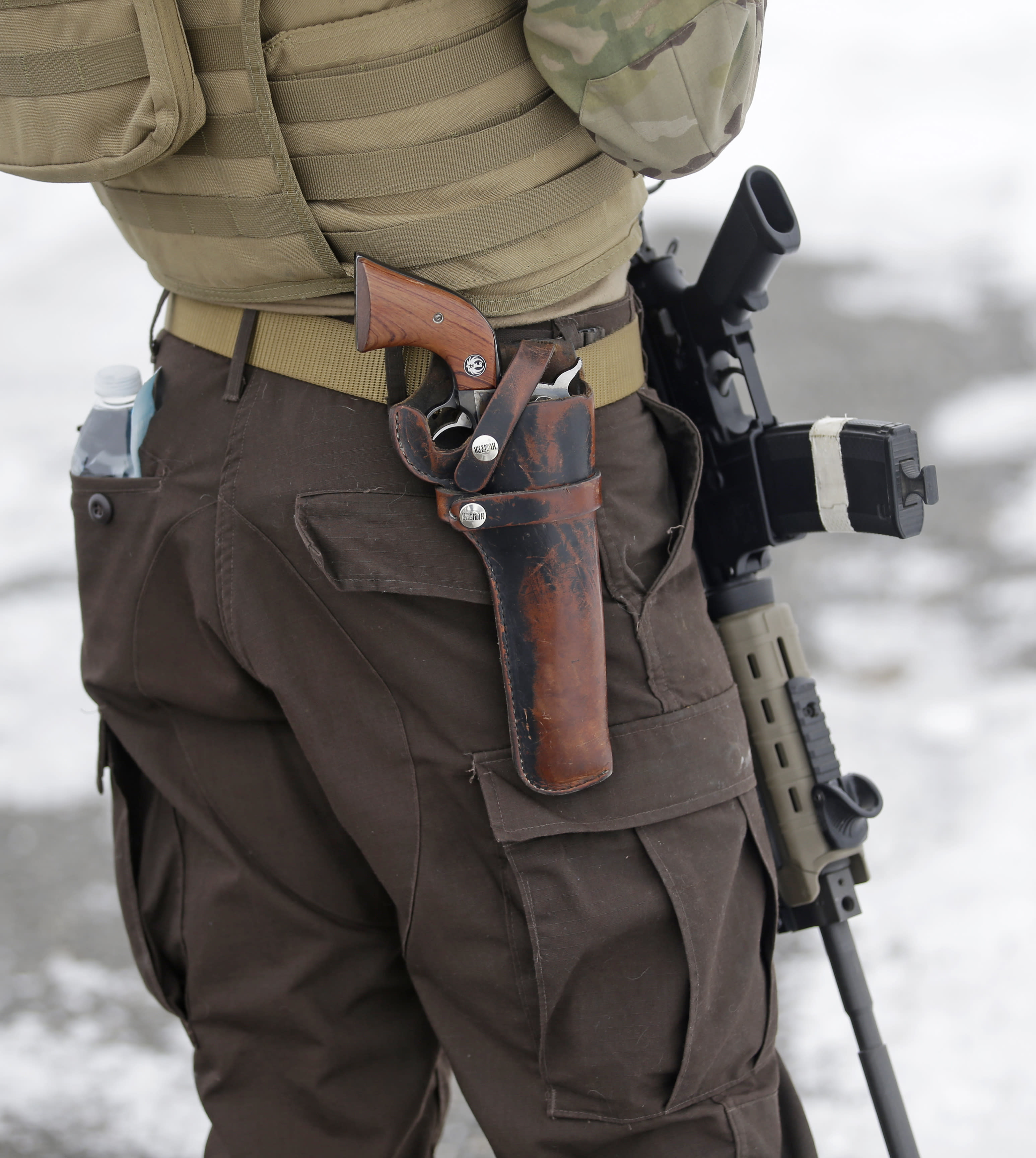 FILE - In this Jan. 9, 2016, file photo, a man stands guard after several organizations arrived at the Malheur National Wildlife Refuge near Burns, Ore. A new report from the Government Accountability Office highlights violence against public lands employees amid heightened tensions with anti-government groups. (AP Photo/Rick Bowmer, File)