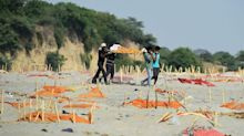 Covid victims' bodies buried in shallow mass graves along banks of India's Ganges