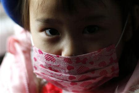A girl wearing a mask sits in a school bus heading to the Emporium kindergarten in Koriyama, west of the tsunami-crippled Fukushima Daiichi nuclear power plant, Fukushima prefecture February 28, 2014. REUTERS/Toru Hanai