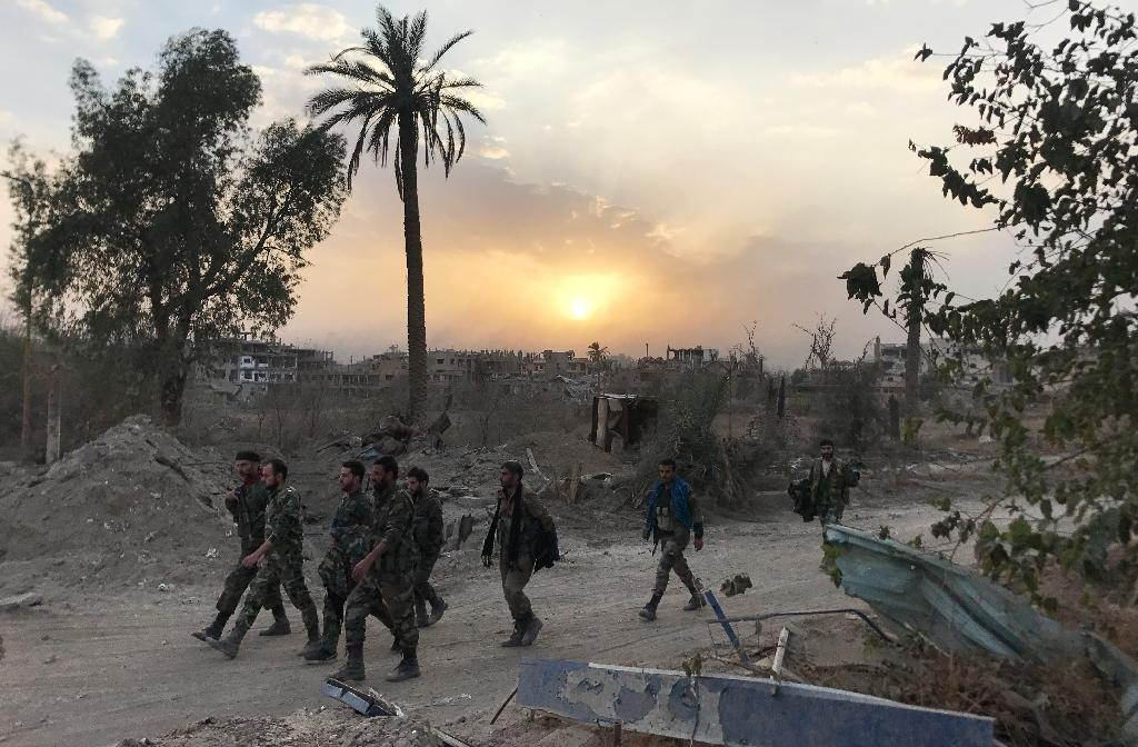 Syrian government forces walk in a district of Deir Ezzor on November 5, 2017, after retaking the city from the Islamic State group but jihadists still hold several villages in the province