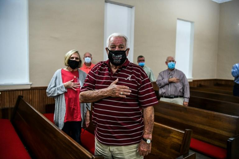 Members of the local Republican Party stand for the national anthem at the county courthouse in Double Springs, Alabama on October 12, 2020