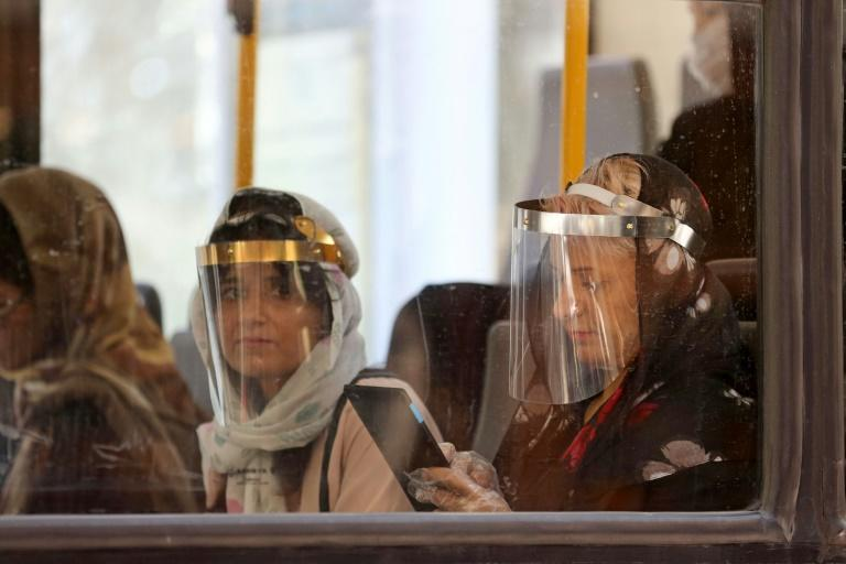 Bus passengers in the Iranian capital Tehran wear face shields against the Middle East's deadliest coronavirus outbreak
