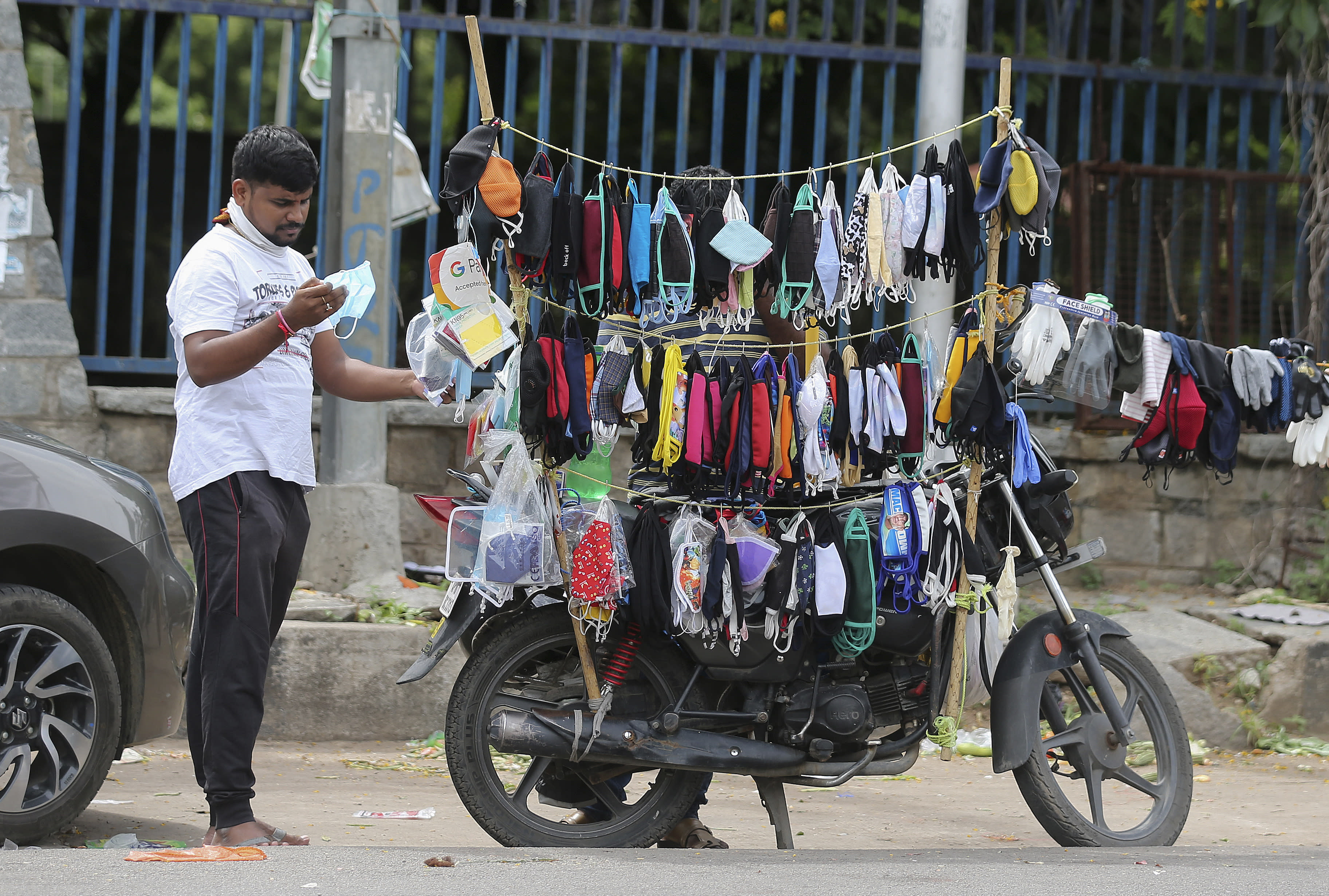 An Indian man checks a face mask before buying it in Hyderabad, India, Tuesday, Aug. 4, 2020. India is the third hardest-hit country by the pandemic in the world after the United States and Brazil. (AP Photo/Mahesh Kumar A.)