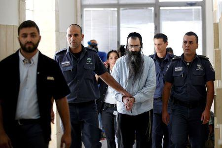 REFILE - CORRECTING TYPOYishai Schlissel (C), convicted of killing a woman during the 2015 Jerusalem Gay Pride Parade, is escorted by security personnel before he is sentenced at the Jerusalem District Court June 26,2016. REUTERS/Ronen Zvulun