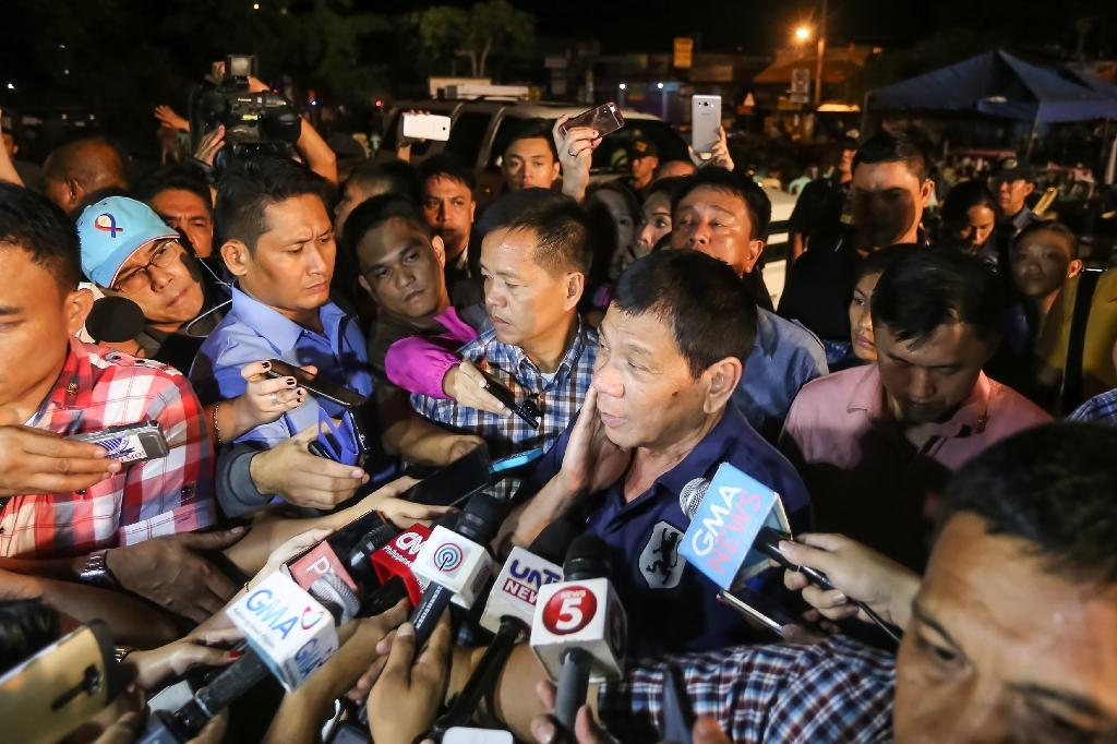 Philippine President Rodrigo Duterte speaks to the media as he visits the site of an explosion at a nigth market in Davao City, on the southern island of Mindanao, early on September 3, 2016 (AFP Photo/Manman Dejeto)
