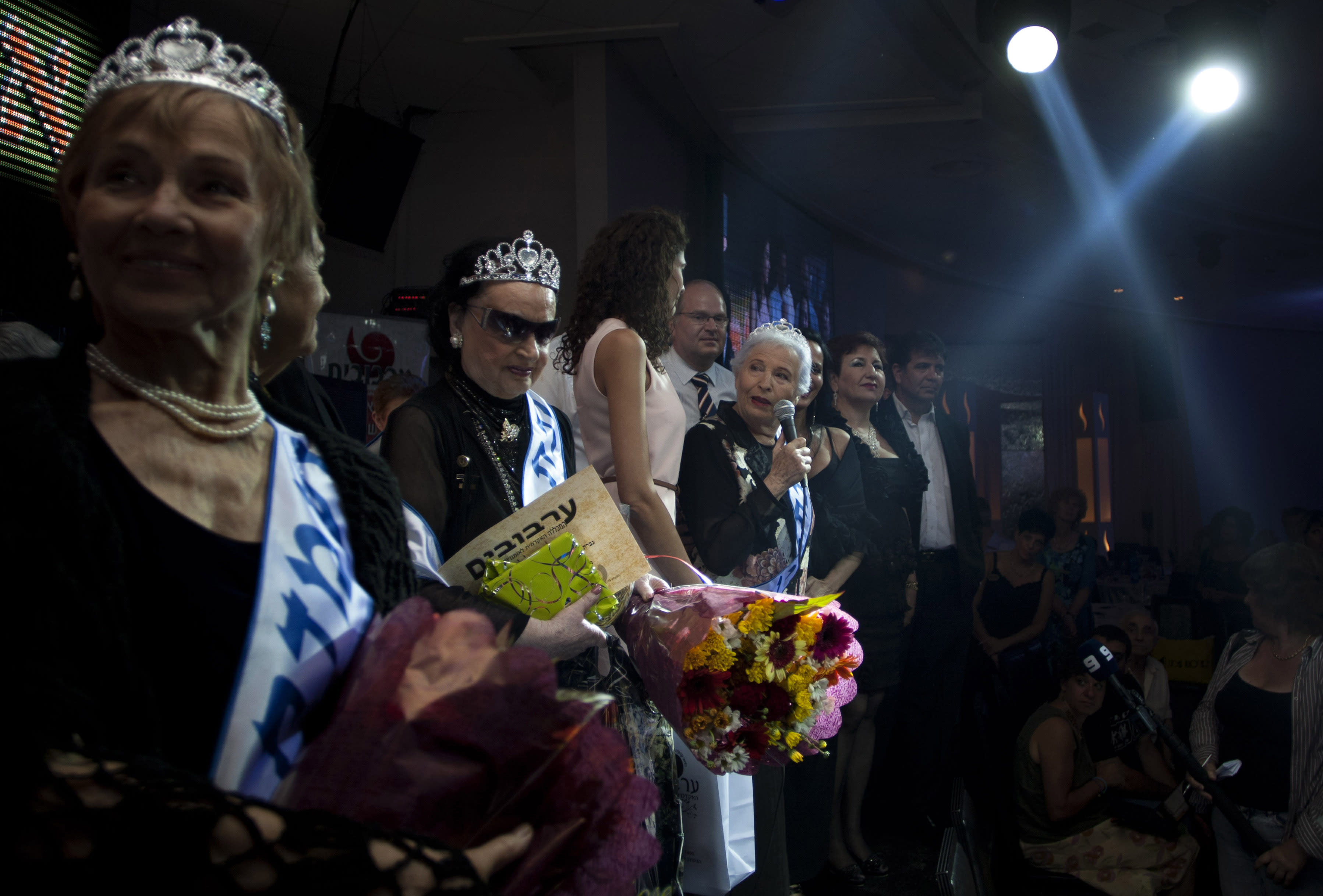 """Hava Hershkovitz, third from right, a Holocaust survivor and winner of a beauty pageant, speaks to the crowd in the northern Israeli city of Haifa, Thursday, June 28, 2012. Fourteen women who lived through the horrors of World War II paraded on stage Thursday night in an unusual pageant, vying for the honor of being Israel's first """"Miss Holocaust Survivor."""" (AP Photo/Sebastian Scheiner)"""