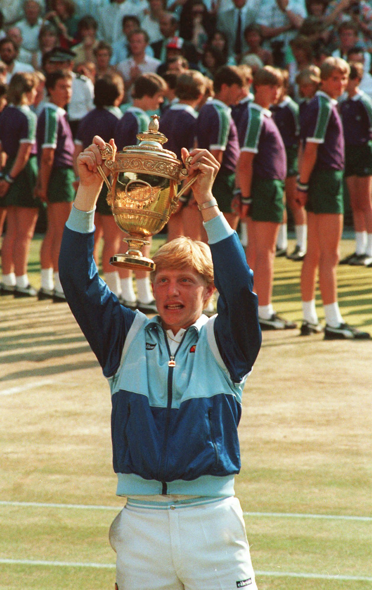 FILE - In this July 7, 1985, file photo, 17-year-old Boris Becker holds the Wimbledon trophy aloft after defeating South Africa's Kevin Curren. (AP Photo/Bob Dear, File)