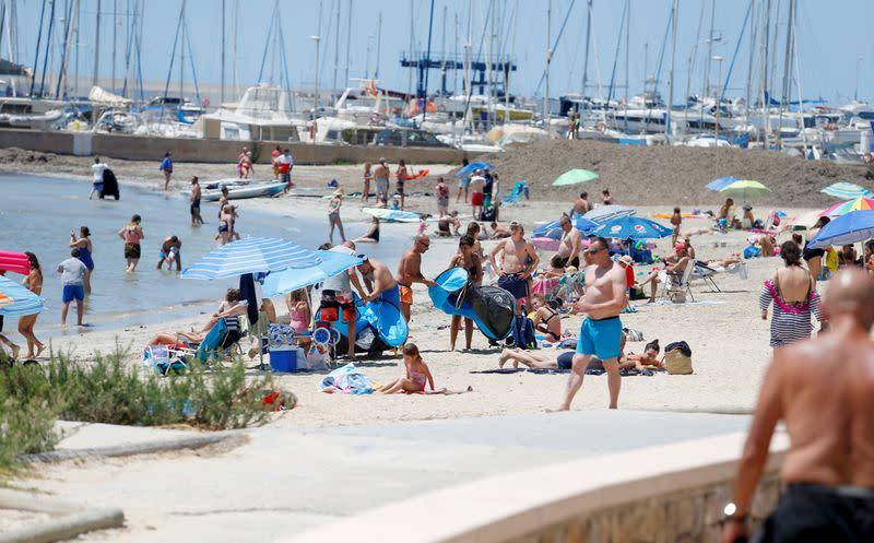 FILE PHOTO: People sunbathe on Playa de Palma beach in Mallorca