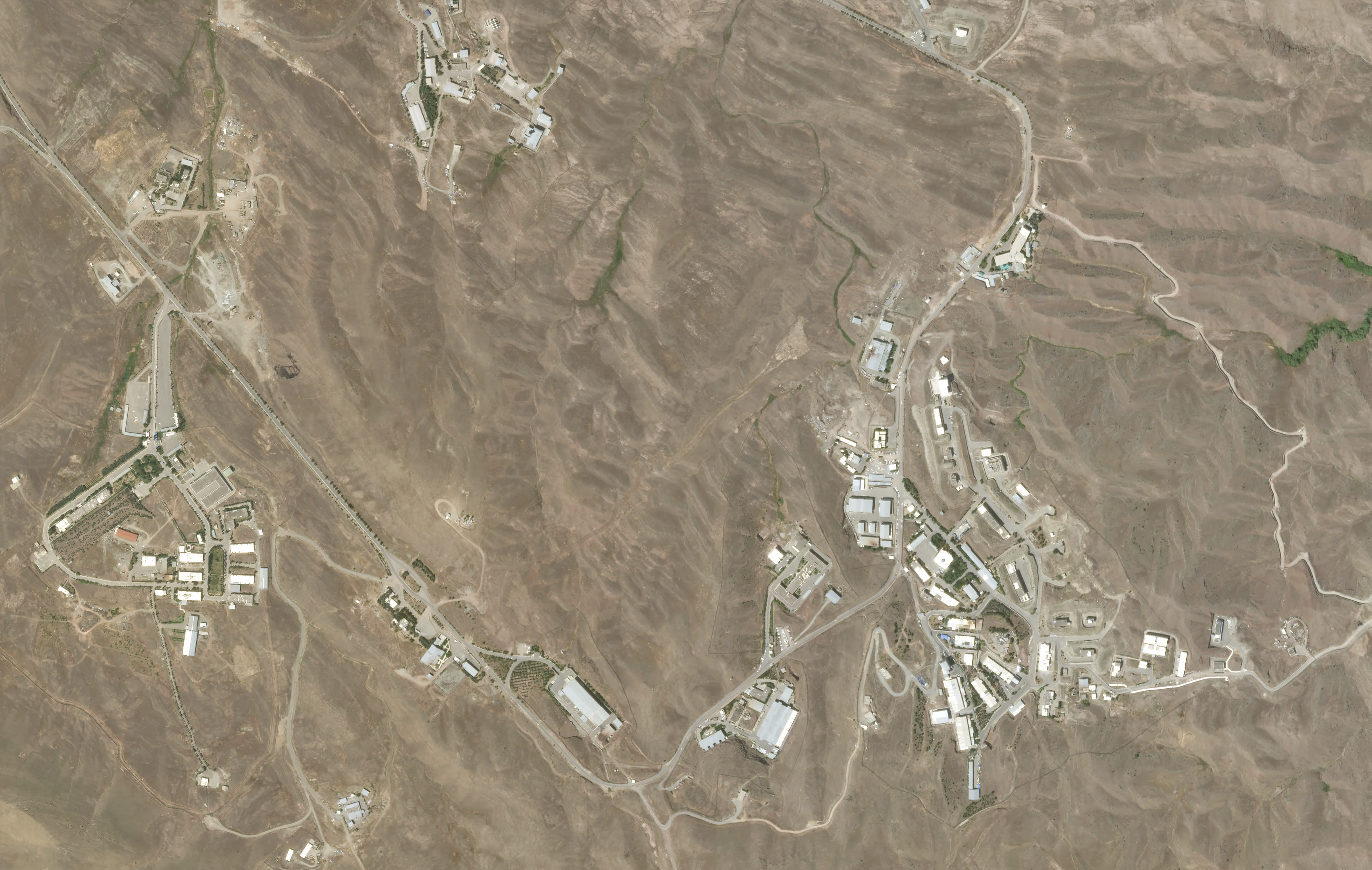 This June 10, 2020, satellite image from Planet Labs shows the site of a June 26, 2020 explosion that rattled Iran's capital before the blast. Analysts say the blast came from an area in Tehran's eastern mountains they hides a underground tunnel system and missile production sites. The explosion appears to have charred hundreds of meters of scrubland. (Planet Labs via AP)
