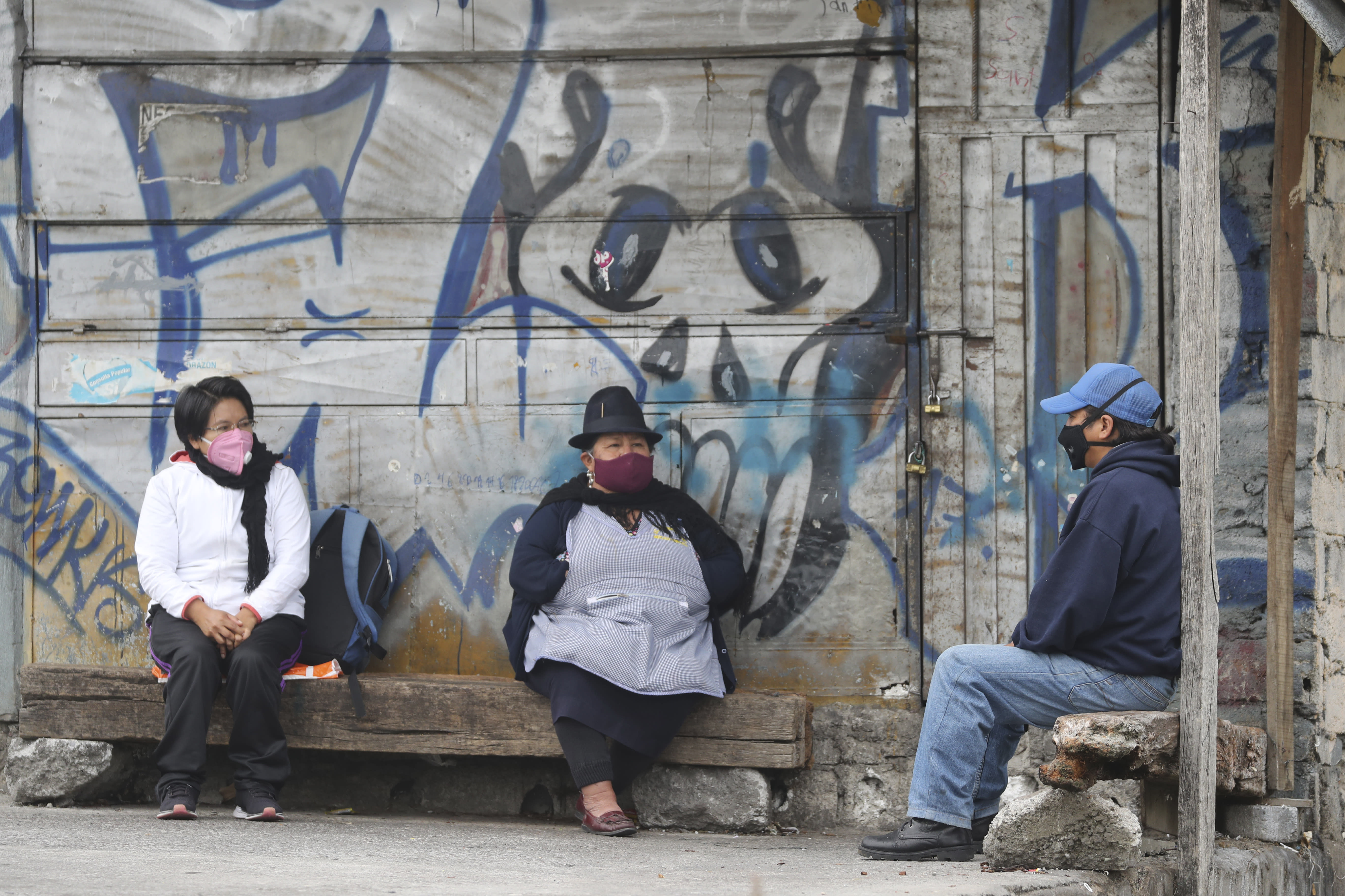 People wearing protective face masks, wait their turn to get COVID-19 tests, while sitting on makeshift benches outside a health clinic in Quito, Ecuador, Wednesday, July 29, 2020. The Ecuadorian capital has experienced a surge in COVID-19 cases since the government started to reopen the economy last month. (AP Photo/Dolores Ochoa)