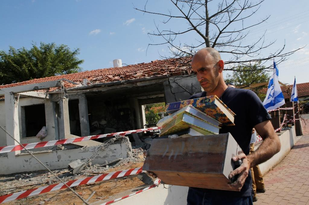 An Israeli man removes on November 13, 2018 belongings from a house in the southern Israeli city of Ashkelon damaged by a rocket fired from the Gaza Strip (AFP Photo/GIL COHEN-MAGEN)