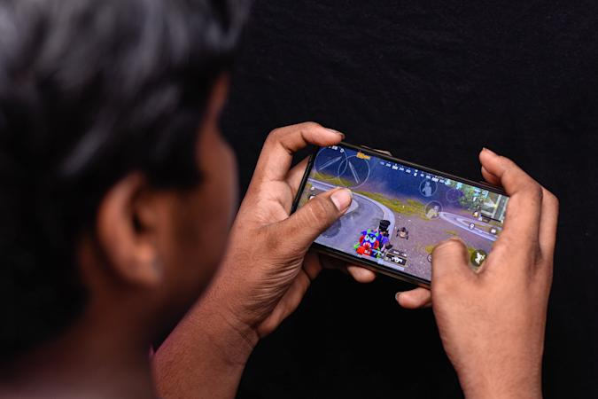 NEW DELHI, INDIA - 2020/07/29: In this photo illustration, a boy playing PUBG (PlayerUnknown's Battlegrounds) on his smartphone. Indian government is considering a ban on the battle royale format games over data security concerns. (Photo Illustration by Ajay Kumar/SOPA Images/LightRocket via Getty Images)