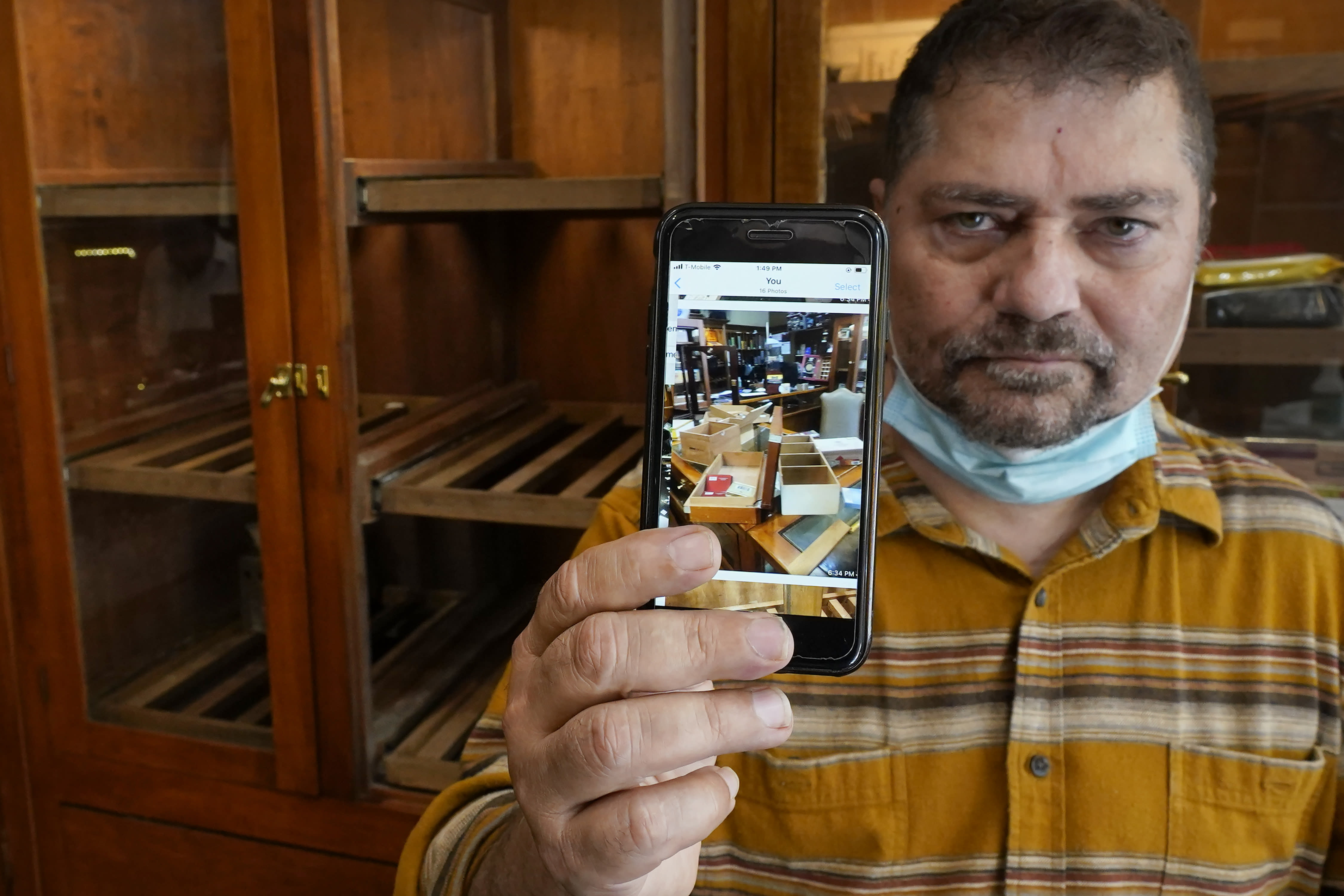 """Neil Mehra, owner of the Hubbard & State Cigar Shop, near Chicago' Magnificent Mile, stands nears an empty humidor on Wednesday, Aug. 12, 2019, holding a cell phone image of his shop after looters stole thousands of dollars worth of merchandise and cash. """"When I got here and saw what they'd done, I almost cried,"""" said Mehra. """"This is my life. I really don't know if we're going to survive this."""" (AP Photo/Charles Rex Arbogast)"""