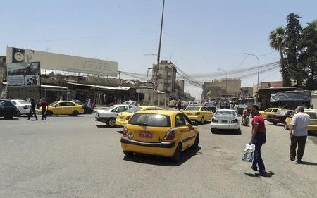 Vehicles drive on a street in the city of Mosul