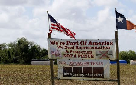 A sign sits on display in a farm field near the U.S.-Mexico border outside Brownsville, Texas September 2, 2014. REUTERS/Rick Wilking