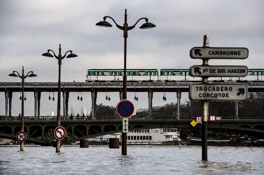 A metro train crosses a bridge over the swollen Seine river in front of partially submerged signs in Paris (AFP Photo/CHRISTOPHE ARCHAMBAULT)