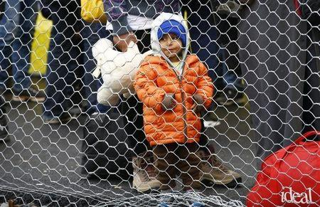 A migrant boy waits to cross the border from Slovenia into Spielfeld in Austria