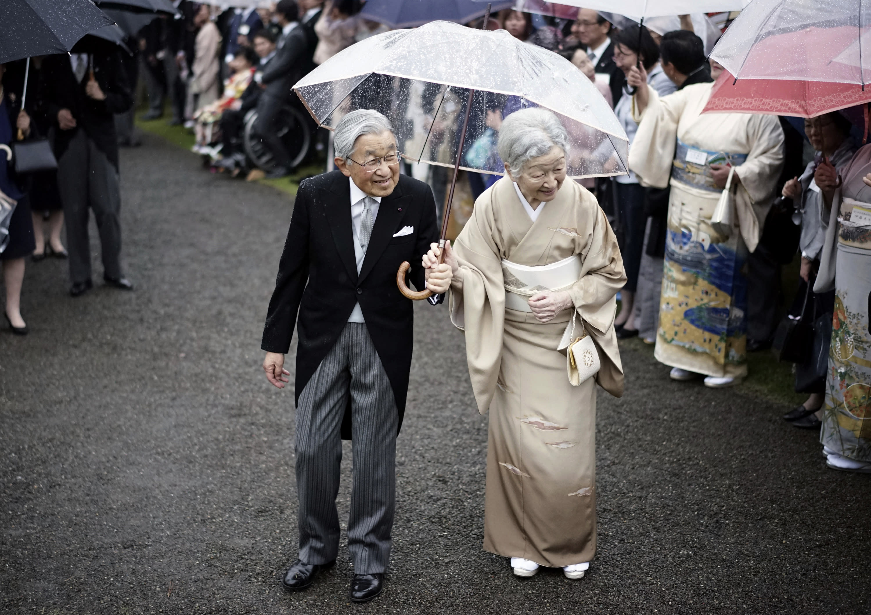 FILE - In this Nov. 9, 2018, file photo, Japan's Emperor Akihito, left, and Empress Michiko, right, greet the guests during the autumn garden party at the Akasaka Palace imperial garden in Tokyo. On May 1, 2019, when Crown Prince Naruhito becomes the new emperor. Naruhito will receive a much more important inheritance: The deep respect and affection his father, soon-to-abdicate Emperor Akihito, has accumulated over his three-decade reign. (AP Photo/Eugene Hoshiko, File)