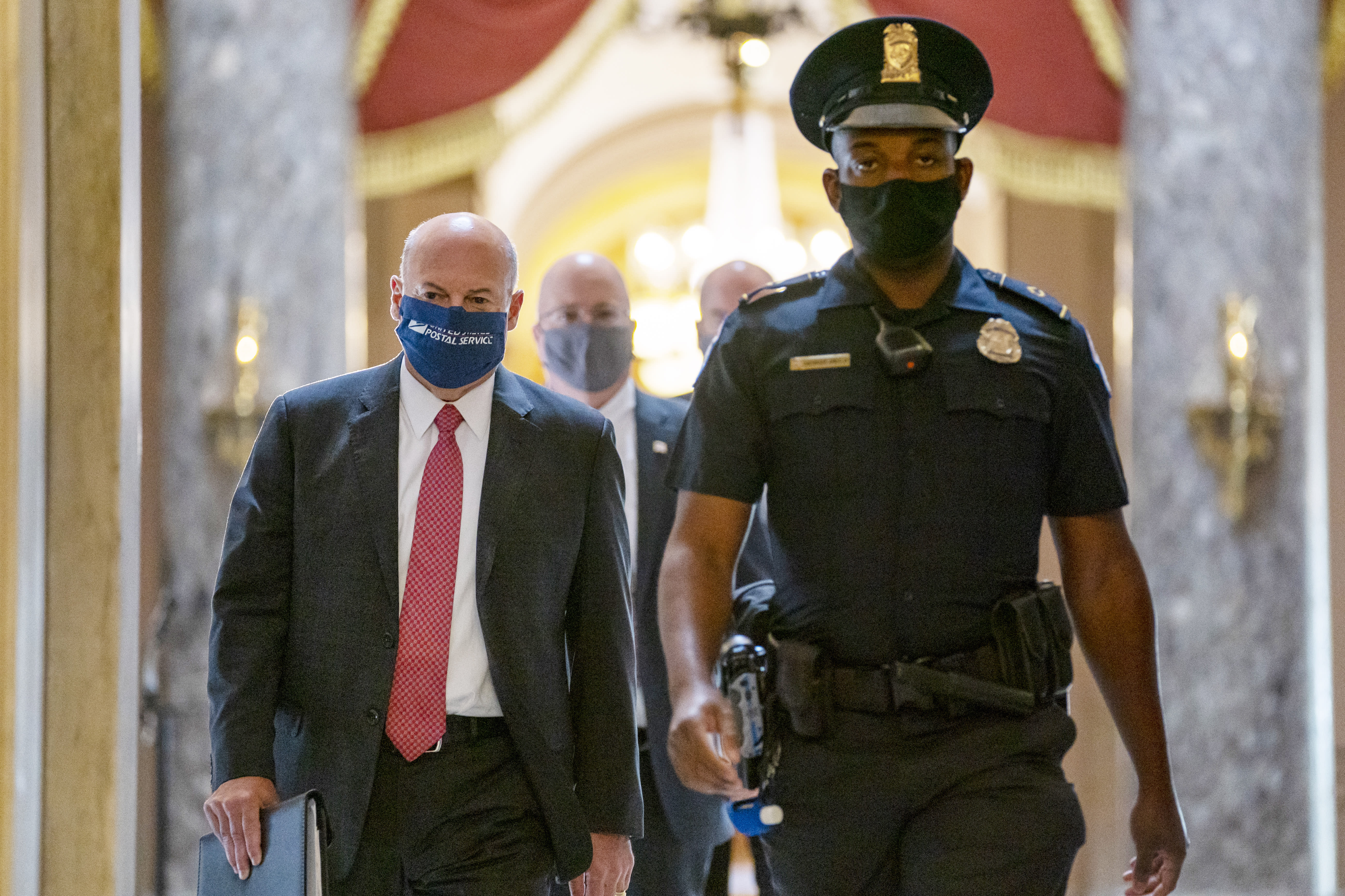 Postmaster General Louis DeJoy, left, is escorted to House Speaker Nancy Pelosi's office on Capitol Hill in Washington, Wednesday, Aug. 5, 2020. Some clarity is beginning to emerge from the bipartisan Washington talks on a huge COVID-19 response bill. An exchange of offers and meeting devoted to the Postal Service on Wednesday indicates the White House is moving slightly in House Speaker Nancy Pelosi's direction on issues like aid to states and local governments and unemployment insurance benefits. But the negotiations have a long ways to go. (AP Photo/Carolyn Kaster)