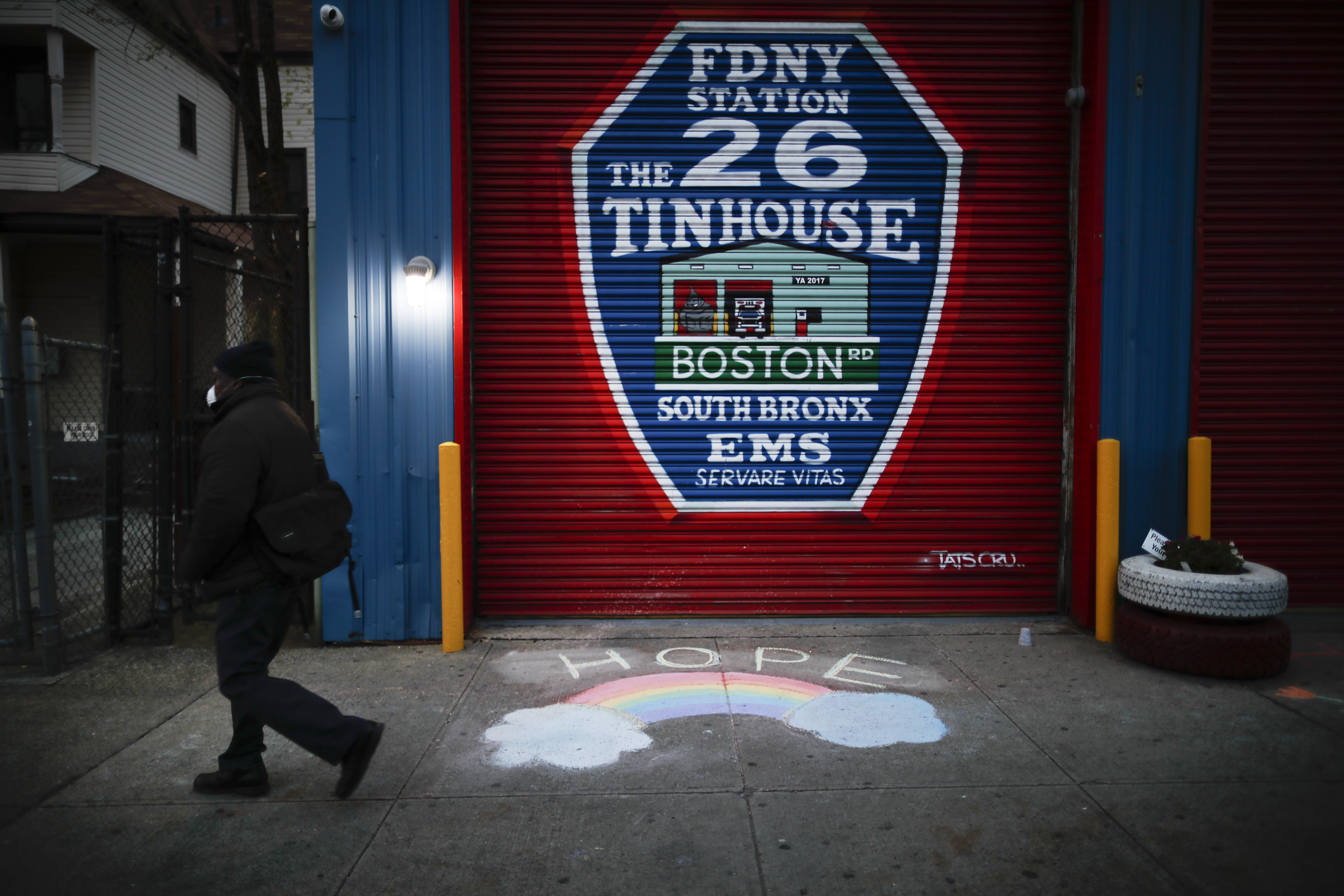 """A pedestrian wearing personal protective equipment to protect against the spread of coronavirus, passes EMS station 26, the Tinhouse"""" Thursday, April 23, 2020 in the Bronx borough of New York. (AP Photo/John Minchillo)"""