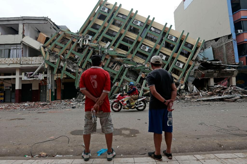 Men look at a destroyed building in the town of Portoviejo, Ecuador, on April 21, 2016 (AFP Photo/Juan Cevallos)