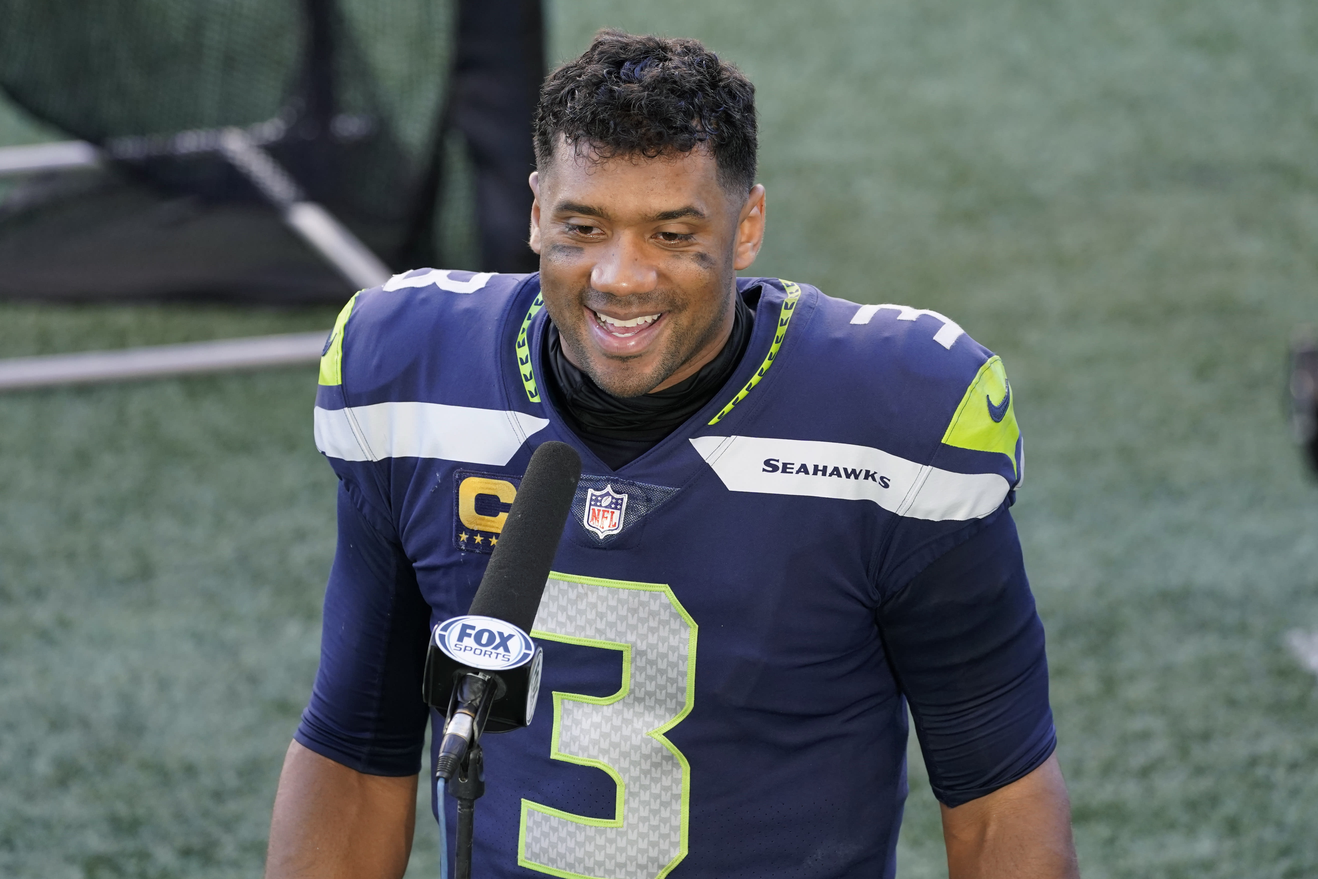 Seattle Seahawks quarterback Russell Wilson smiles during a post-game interview after an NFL football game against the Dallas Cowboys, Sunday, Sept. 27, 2020, in Seattle. The Seahawks won 38-31. (AP Photo/Elaine Thompson)