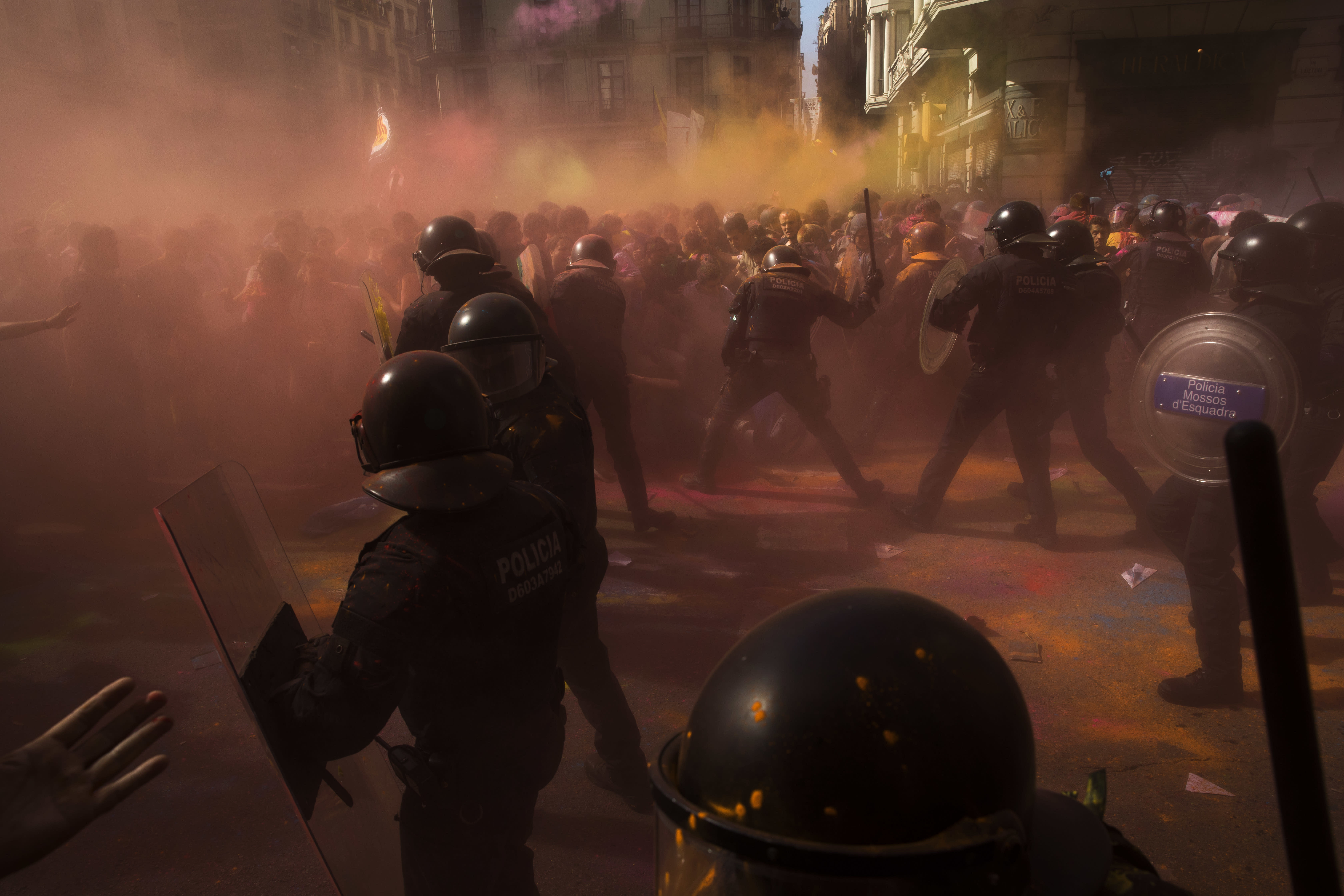 Catalan police officers clash with pro independence demonstrators on their way to meet demonstrations by member and supporters of National Police and Guardia Civil, as colored powder is seen in the air after being thrown by protesters, in Barcelona on Saturday, Sept. 29, 2018. (AP Photo/Emilio Morenatti)