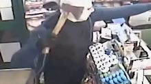 CCTV shows masked robbers threaten shop worker with axe and hammer before fleeing with cash