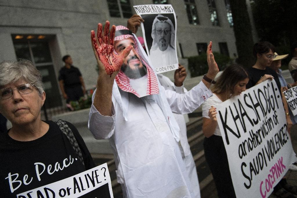 A demonstrator dressed as Saudi Crown Prince Mohammed bin Salman (C) with blood on his hands protests outside the Saudi Embassy in Washington, DC, on October 8, 2018 (AFP Photo/Jim WATSON)