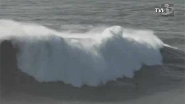 Look hard - There's a surfer on that massive wave!