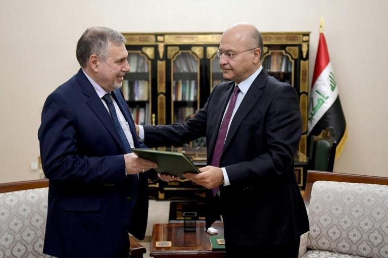 Iraqi President Barham Salih (R) presents Mohammad Allawi, a former communications minister, with the decree to appoint him prime minister (AFP Photo/-)