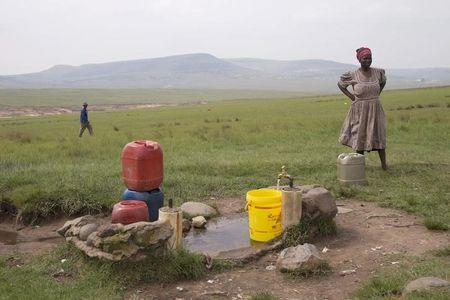 A woman fills a bucket at the last tap with running water in their village after water to the other communal taps was cut off due to drought in Qwabe