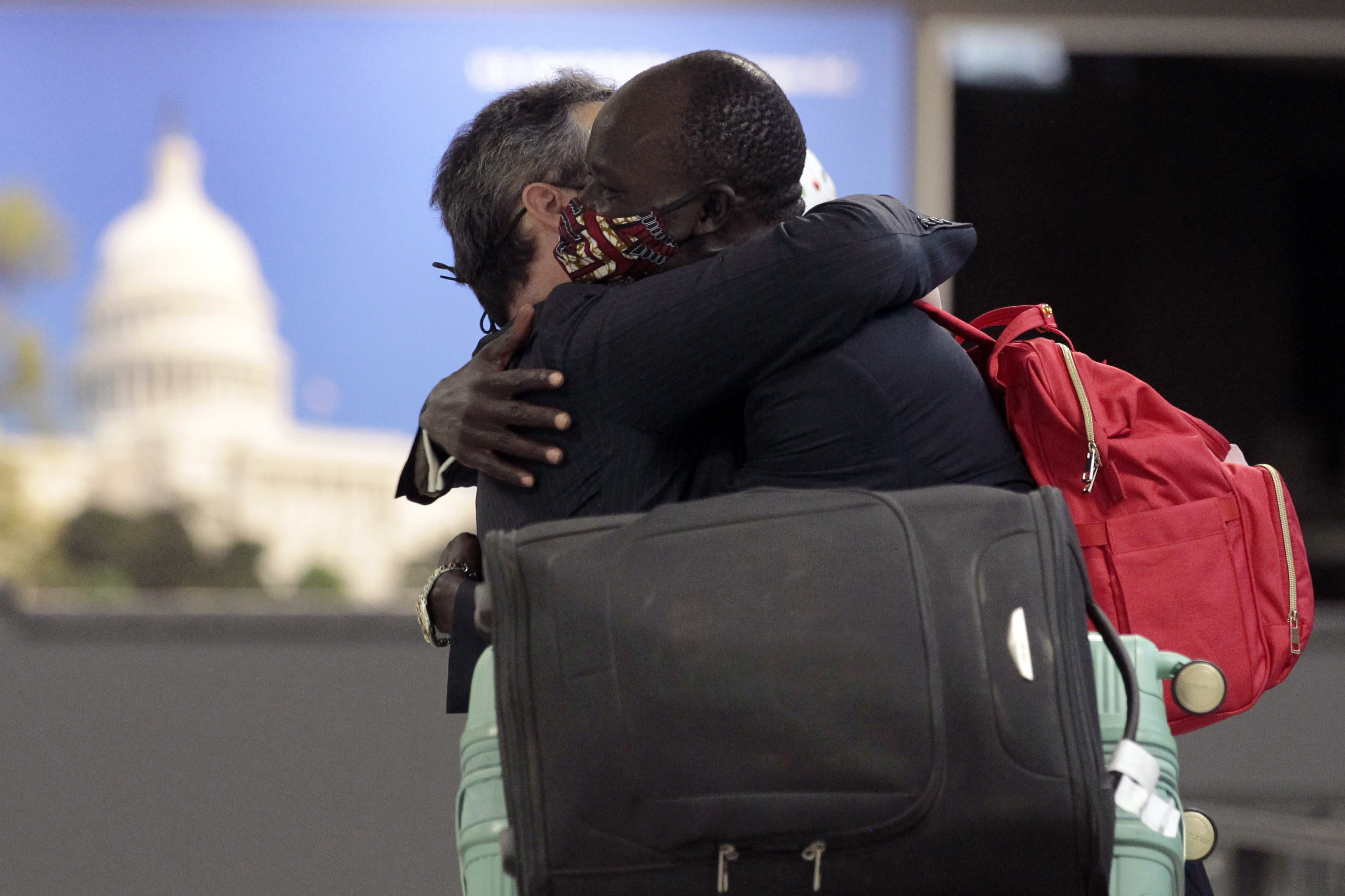 Peter Biar Ajak, right, hugs his lawyer Jared Genser upon his arrival at Washington Dulles International Airport in Chantilly, Va., Thursday, July 23, 2020. (AP Photo/Luis M. Alvarez)