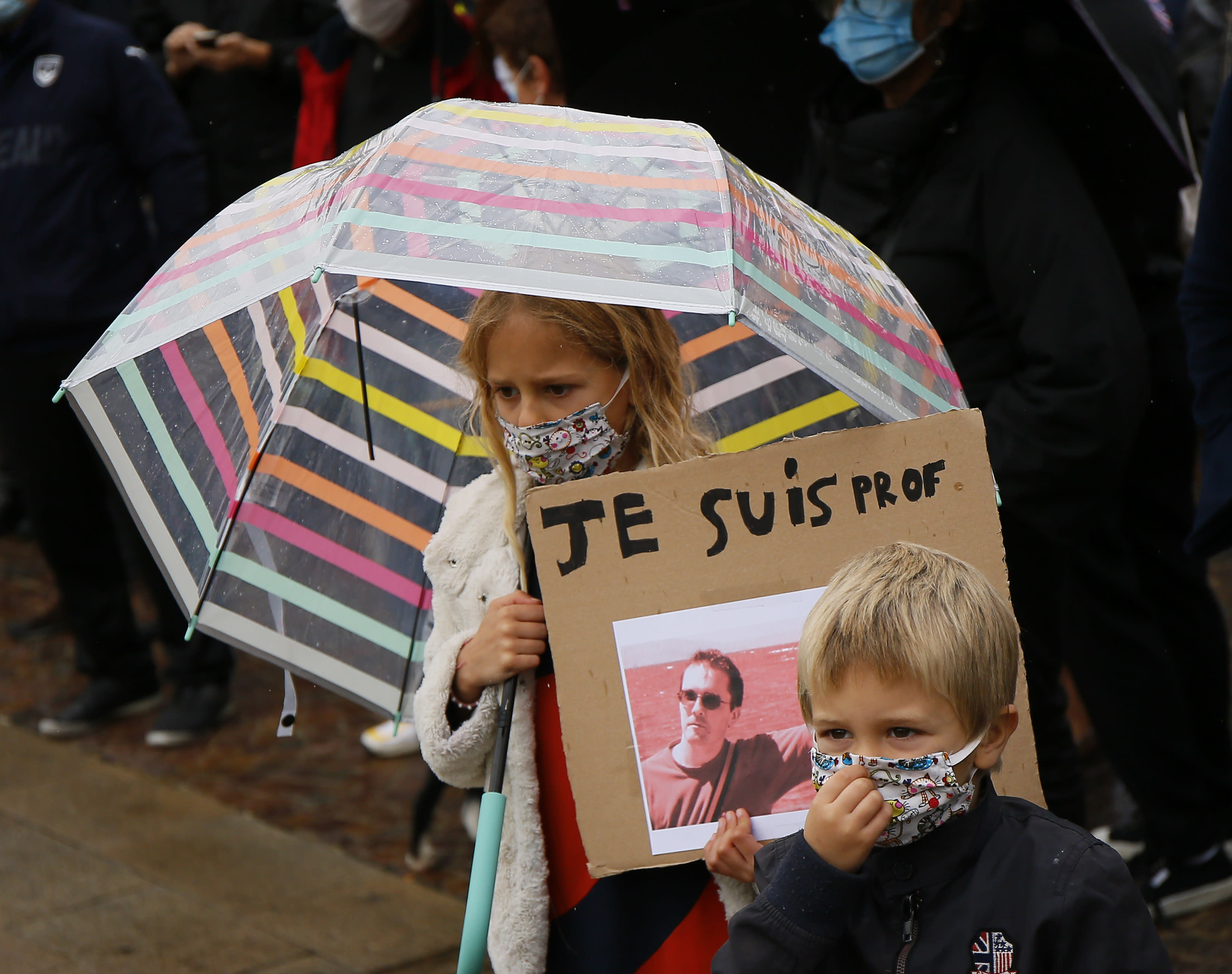 A child holds up a a poster of Samuel Paty as people gather on Republique square in Lille, northern France, Sunday Oct. 18, 2020. Demonstrators in France on Sunday took part in gatherings in support of freedom of speech and in tribute to a history teacher who was beheaded near Paris after discussing caricatures of Islam's Prophet Muhammad with his class. (AP Photo/Michel Spingler)