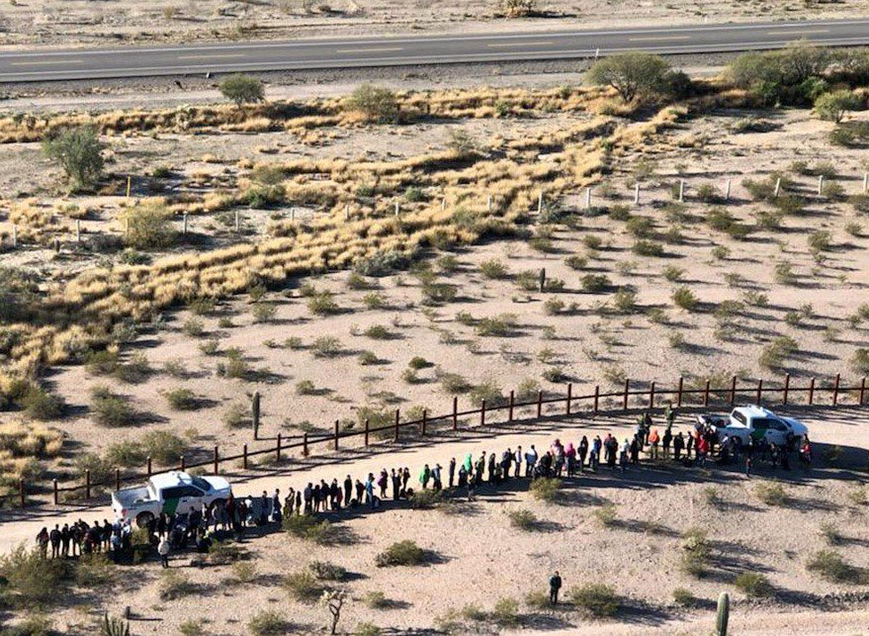 File - In this Thursday, Feb. 7, 2019, file aerial image released by the U.S. Customs and Border Protection, migrants, apprehended after illegally crossing along the U.S.-Mexico border near Lukeville, Ariz., are lined up. Mexico is at the top of the image, beyond the border fence. A border activist charged with helping a pair of migrants with water, food and lodging is set to go on trial in U.S. court in Arizona. Defendant Scott Daniel Warren has argued that his spiritual values compel him to help all people in distress. The trial is scheduled to begin Wednesday, May 29, 2019, in Tucson, with the 36-year-old Warren charged with harboring migrants and conspiring to transport and harbor two Mexican men found with him who were in the U.S. illegally. (U.S. Customs and Border Protection via AP, File)